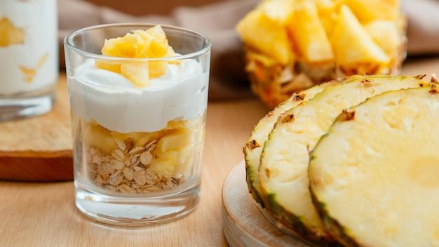Delizioso dessert all'ananas. dessert della colazione con muesli di avena, yogurt greco e ananas a strati in vetro con ingredienti ananas succoso fresco tritato sul tavolo di legno foto d'archivio di alta qualità.
