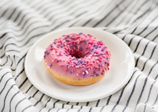 Deliziosa ciambella rosa con glassa e spolverata su un piatto. dessert dolce