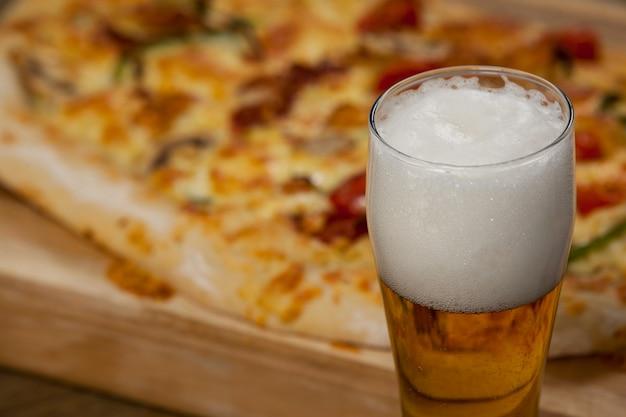 Deliziosa pizza servita sul vassoio della pizza con un bicchiere di birra