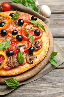Deliziosa pizza servita su tavola di legno