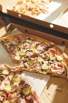 Deliziose fette di pizza in scatola di cartone sul tavolo