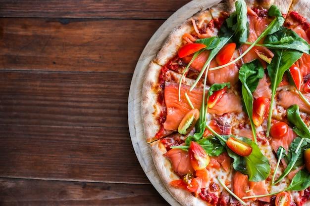 Pizza deliziosa, vista dall'alto. pizza gustosa con pomodori, verdure, formaggio e salmone affumicato sulla tavola di legno