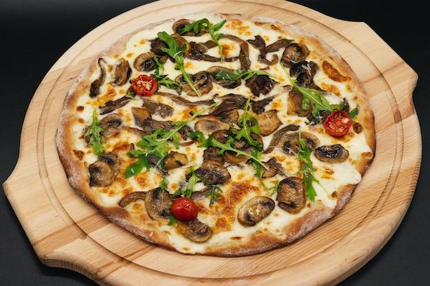 Deliziosa pizza con rucola e pomodori su una tavola