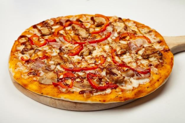 Deliziosa pizza con pancetta e pollo teriyaki servita su un piatto di legno, ingredienti salsa firma, mozzarella, pollo teriyaki, pancetta, pepe bulgaro, salsa teriyaki su bianco.