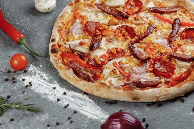 Deliziosa pizza con filetto di pollo, prosciutto, pancetta, salsicce, salsa di pomodoro e mozzarella
