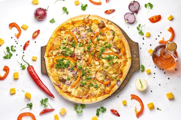 Deliziosa pizza con pollo, cipolla, funghi e peperone dolce sul piatto di legno. sfondo bianco, gustosa composizione.