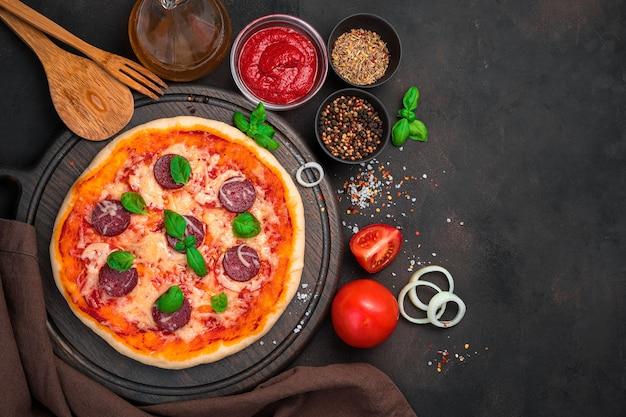 Deliziosa pizza con ingredienti da cucina su uno sfondo di cemento marrone. vista orizzontale con spazio per copiare.