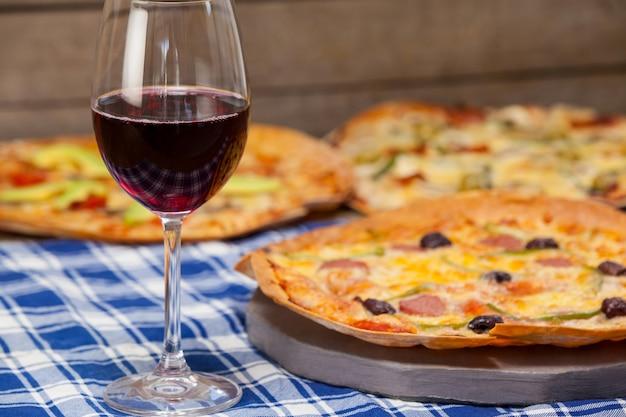 Deliziosa pizza con un bicchiere di vino rosso