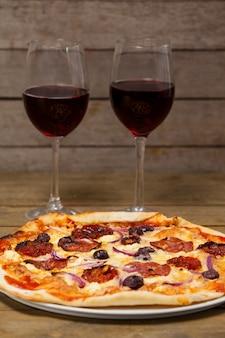 Deliziosa pizza con bicchieri di vino rosso