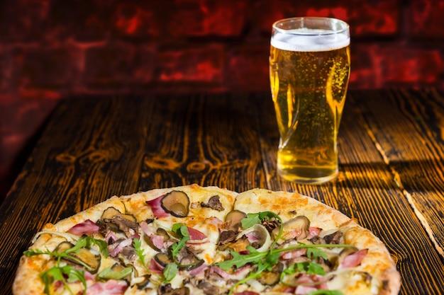 Deliziosa pizza con prosciutto, cipolla e sottaceti sulla tavola di legno vicino a un bicchiere di birra