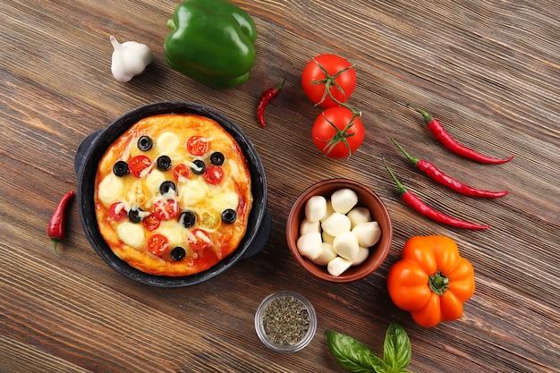 Deliziosa pizza con ingredienti e spezie sul tavolo