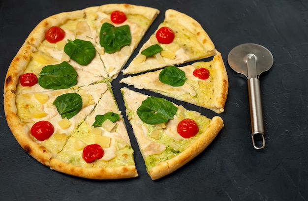 Deliziosa pizza con ananas, pomodori, mozzarella, filetto di pollo su uno sfondo di pietra