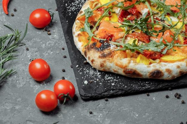 Pizza deliziosa con salmone e verdure. pizza italiana.