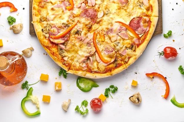 Deliziosa pizza con salsiccia, funghi e peperone sul piatto di legno. sfondo bianco, gustosa composizione.