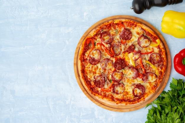 Deliziosa pizza con salsicce su sfondo grigio vista dall'alto