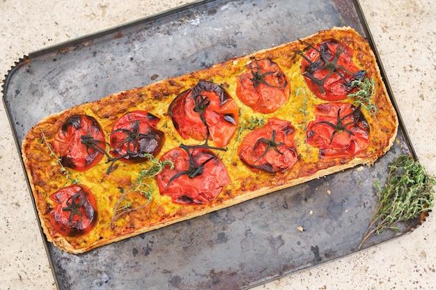 Deliziosa pizza con pomodori in teglia