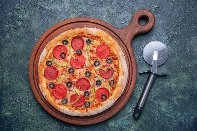 Pizza deliziosa su tagliere di legno su superficie scura isolata