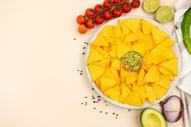 Un delizioso piatto di tortilla nachos con salsa guacamole cipolle rosse pomodori lime olive