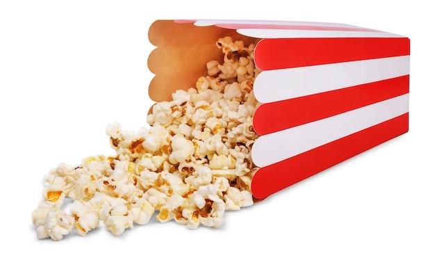 Deliziosi popcorn e secchio di popcorn di carta a strisce rosso rovesciato isolato su sfondo bianco.