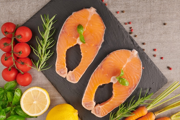 Deliziosa porzione di filetto di salmone fresco con erbe aromatiche, spezie e verdure - cibo sano, dieta o concetto di cucina. concetto nutrizionale equilibrato per un'alimentazione pulita dieta mediterranea flessibile.