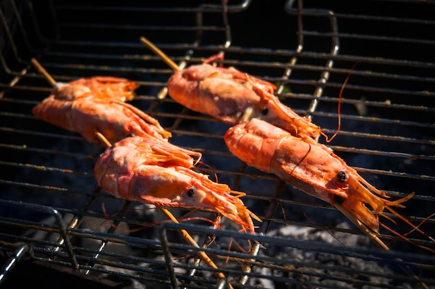 Delizioso spiedo di gamberi alla griglia con fiamme. gamberoni in guscio fritti al fuoco.
