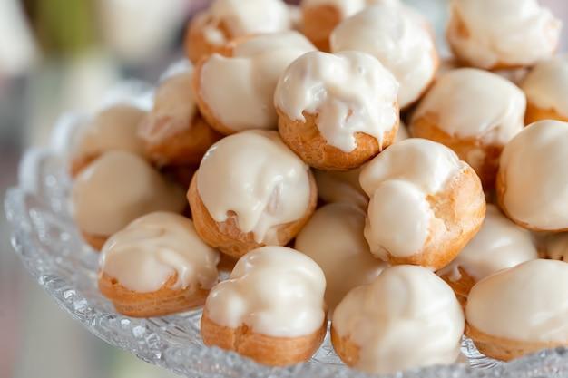 Deliziosi profiteroles su un piatto di cristallo. squisito dessert nuziale. dessert per tè o caffè
