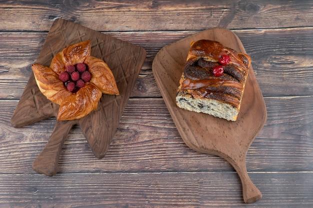 Deliziosa pasticceria ai lamponi e torta ai frutti di bosco su tavola di legno.