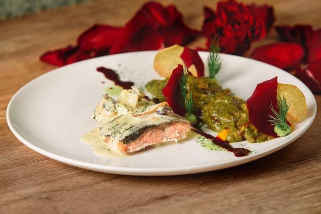 Delizioso filetto di pesce rosso con salsa bianca con verdure in salsa verde su un piatto bianco. un bel piatto da ristorante decorato con petali di rosa.