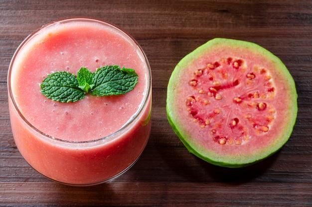 Delizioso succo di guava rosso accanto a una fetta di guava con guaiave e foglie su legno rustico