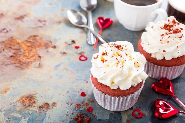 Deliziosi cupcakes di velluto rosso per san valentino sulla vecchia superficie di metallo arrugginito. concetto di cibo per le vacanze. copia spazio