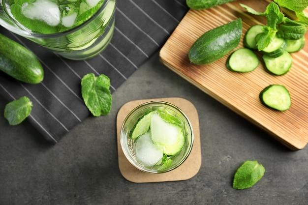 Deliziosa acqua rinfrescante con menta e cetriolo in vetro sul tavolo
