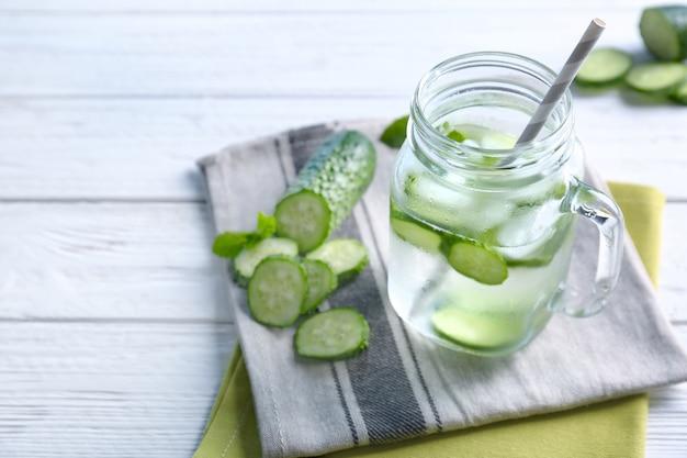 Deliziosa acqua rinfrescante con menta e cetriolo in barattolo di vetro sul tavolo