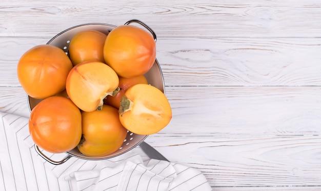 Frutta matura deliziosa del cachi su fondo di legno bianco