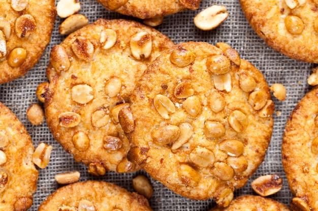 Deliziosi biscotti rotondi da ingredienti diversi, biscotti croccanti con arachidi tostate, sulla superficie di un biscotto fresco rotondo caramello con arachidi