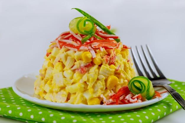 Deliziosa insalata con polpa di granchio, mais, cetriolo e uova. avvicinamento.