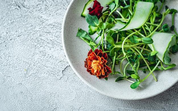 Deliziosa insalata con fiori sul piatto rotondo bianco, vista dall'alto con lo spazio della copia