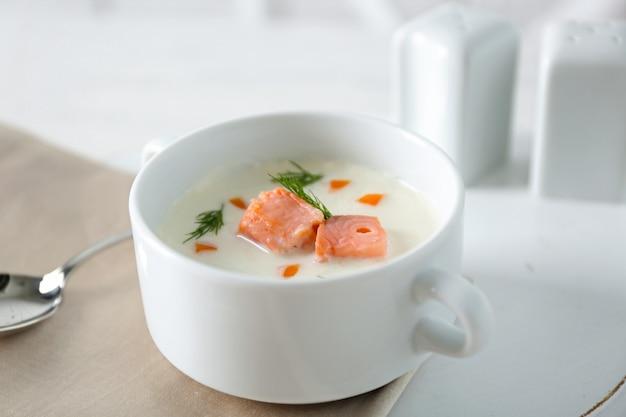 Deliziosa zuppa di crema di salmone sul tavolo bianco servito nel ristorante
