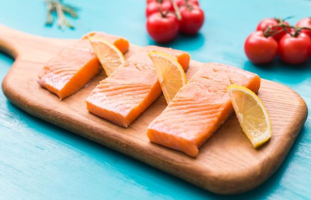 Deliziosa bistecca di color salmone sul tagliere di legno, close-up.
