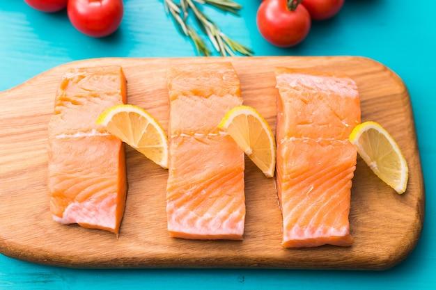 Deliziosa bistecca di color salmone sul tagliere di legno