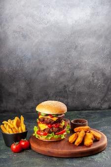 Deliziosi sandwich e bocconcini di pollo su tagliere di legno marrone patatine fritte sulla superficie del ghiaccio con spazio libero free