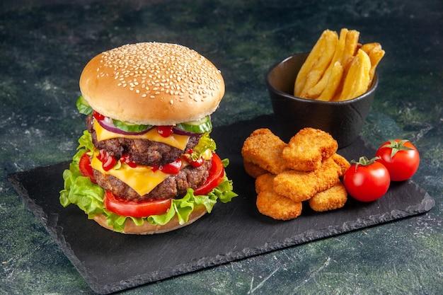 Delizioso panino su vassoio di colore scuro e pepite di pollo patatine fritte su superficie nera