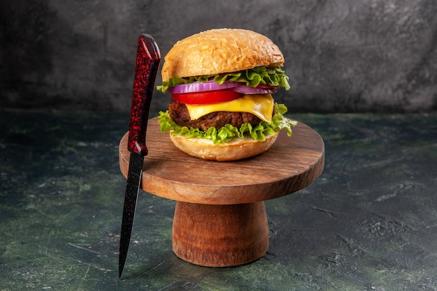 Panino delizioso e forchetta rossa su tavola di legno su superficie di colore misto scuro con spazio libero