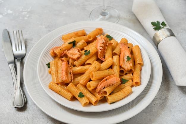 Deliziosa pasta di pesce in zolla bianca su un tavolo in pietra grigia vista dall'alto