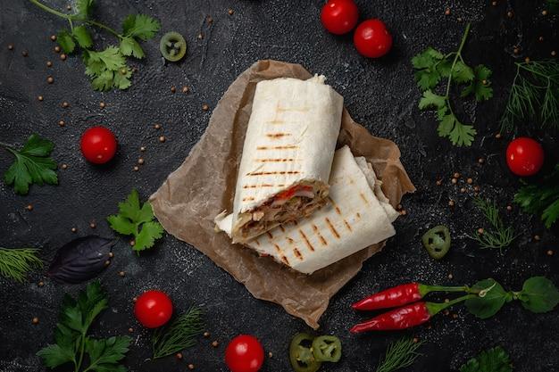 Deliziosi tacos di shawarma e lavash su un tavolo di pietra scura. ristorante fast food. opzione salutare di fast food. gustosi panini freschi con carne di manzo e verdure, spuntino tradizionale mediorientale