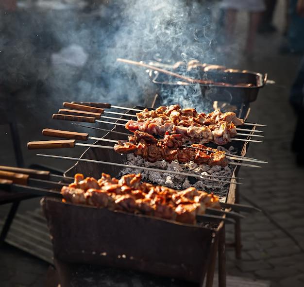 Deliziose griglie di shish kebab sul barbecue in fumo