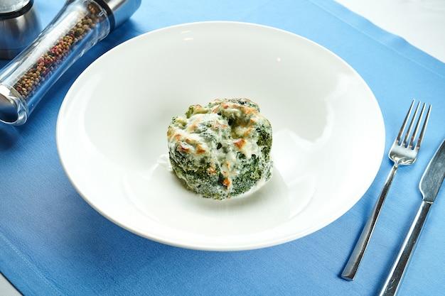 Delizioso contorno per i secondi piatti - broccoli al forno con formaggio fuso in un piatto bianco su una tovaglia blu