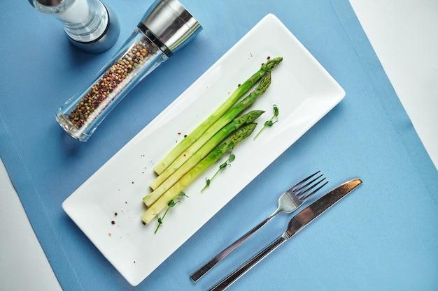 Delizioso contorno per i primi piatti - asparagi bolliti con microgreen in un piatto bianco su una tovaglia blu
