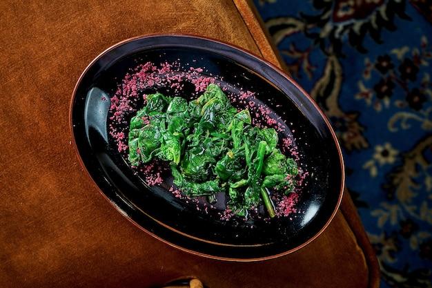 Delizioso contorno per i secondi piatti - spinaci in umido in crema in un piatto nero. vista dall'alto