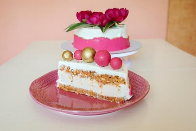 Deliziosa fetta di torta, desset cheesecake con bisquit di carote sul piatto rosa davanti all'appetitosa torta decorata con fiori di peonia.