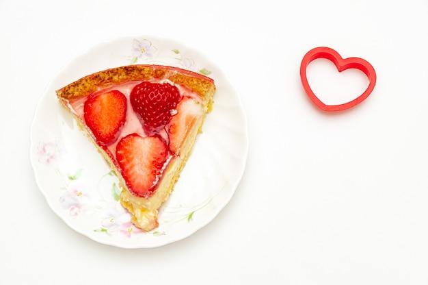 Deliziosa fetta di torta di fragole fatta in casa con oggetto a forma di cuore sul lato